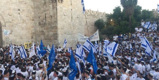 """(Ismael Mohamad / United Press International) Video: Israeli mobs celebrate """"Jerusalem Day"""" with anti-Palestinian rampage in Old City Submitted by Ali Abunimah on Mon, 05/18/2015 - 11:48 Lehava' s gang, """"Jerusalem day"""", 17.5.2015 Note: To see English subtitles, please be sure to click the """"cc"""" button on the YouTube videos included in this post. Thousands of young Israelis, many of them children, rampaged through the Old City of occupied Jerusalem on Sunday chanting """"Death to the Arabs"""" and other racist and anti-Muslim slogans. Some attacked bystanders and journalists and banged on the shutters of Palestinian stores that had been ordered to close at midday. The mob march was the climax of """"Jerusalem Day,"""" an Israeli national holiday to celebrate the occupation of the eastern part of the city in 1967. Zionist militias ethnically cleansed and captured the western sector of Jerusalem in 1948. Under international law, Israel's purported annexation of Jerusalem following the 1967 conquest is null and void and is not recognized by any country in the world. Racist chants Sunday's violent scenes began as occupation forces allowed large numbers of religious and nationalist Israeli Jews to flow into into the area of the Damascus Gate in the late afternoon. This is an entrance to the walled Old City that was long a bustling market for Palestinians from surrounding villages until Israel made access to the city virtually impossible for millions of Palestinians in the occupied West Bank. 2015-5-17-damascus-gate.jpg Israelis, many chanting racist slogans, rally at the Damascus Gate before marching into Jerusalem's Old City, 17 May. (Charlotte Silver)"""